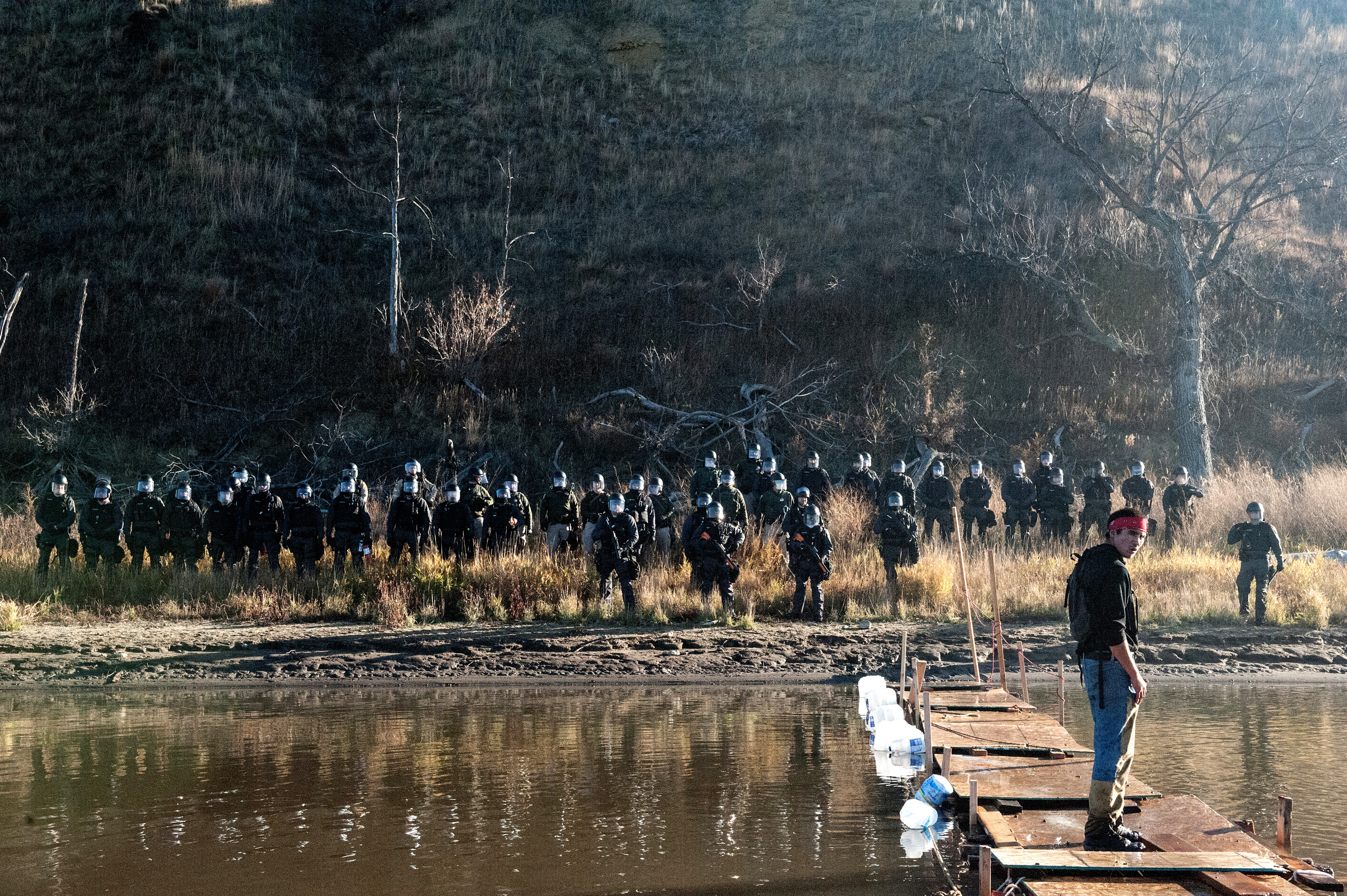 A man stands on a makeshift bridge over the Cannonball River while police officers stand on the opposite shore