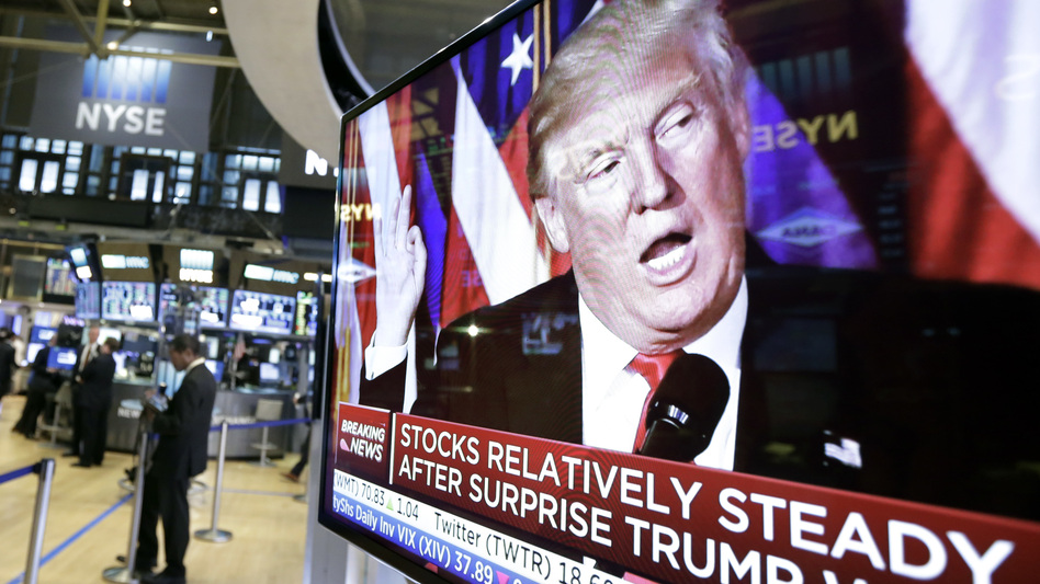 An image of President-elect Donald Trump appears Wednesday on a television screen on the floor of the New York Stock Exchange. Business leaders are taking a wait-and-see approach to his administration. (Richard Drew/AP)