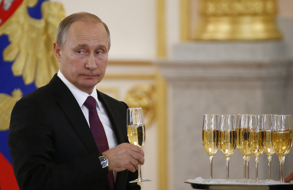 """Russian President Vladimir Putin holds a drink Wednesday at a Kremlin ceremony where he welcomed foreign ambassadors who recently arrived in Moscow. Putin said Moscow wants to restore good relations with the United States in the wake of the election of Donald Trump. But, he added, the current friction """"is not our fault."""" (Sergei Karpukhin/AP)"""