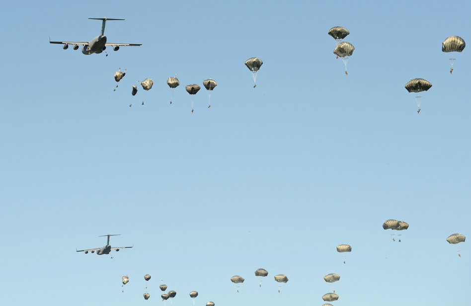 U.S. military planes drop paratroopers during a multi-national jump that includes soldiers from the U.S., Britain and Poland on June 7, near Torum, Poland. U.S. President-elect Donald Trump has questioned the value of the NATO alliances, raising worries among many European countries. (Alik Keplicz/AP)