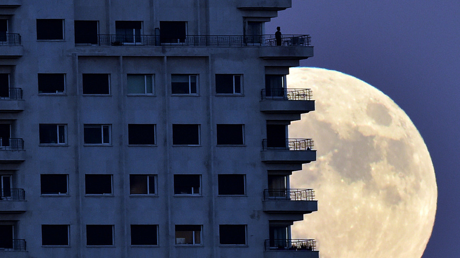 With the Nov. 13 supermoon rising in the background, a man looks out from a balcony in Madrid. At its closest pass to Earth, the full moon can look up to 14 percent bigger and 30 percent brighter, NASA says. (Gerard Julien/AFP/Getty Images)