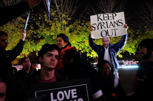 """A counterdemonstrator holds a sign during a gathering in New York City to show solidarity with Syrian and Iraqi refugees last year. Donald Trump's hard-line campaign rhetoric singled out Syrian refugees. """"If I win,"""" he told a New Hampshire rally, """"they are going back."""""""