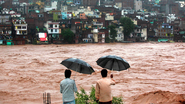 The flood-swollen Tawi River rages past the city of Jammu in northern India in 2014.