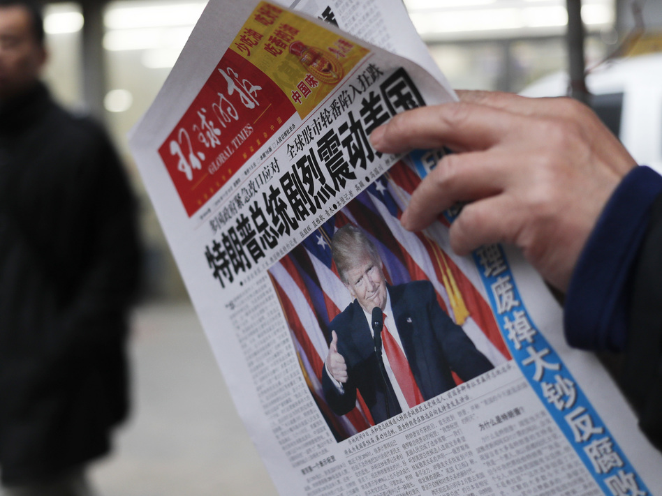 """A Chinese newspaper headline says """"U.S. President-elect Donald Trump delivers a mighty shock to America."""" Trump has promised to label China a currency manipulator, which would pave the way to imposing high tariffs on Chinese imports. (Andy Wong/AP)"""
