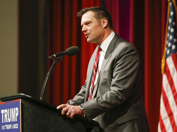Kansas Secretary of State Kris Kobach supports Donald Trump during a rally in Wichita, Kan.