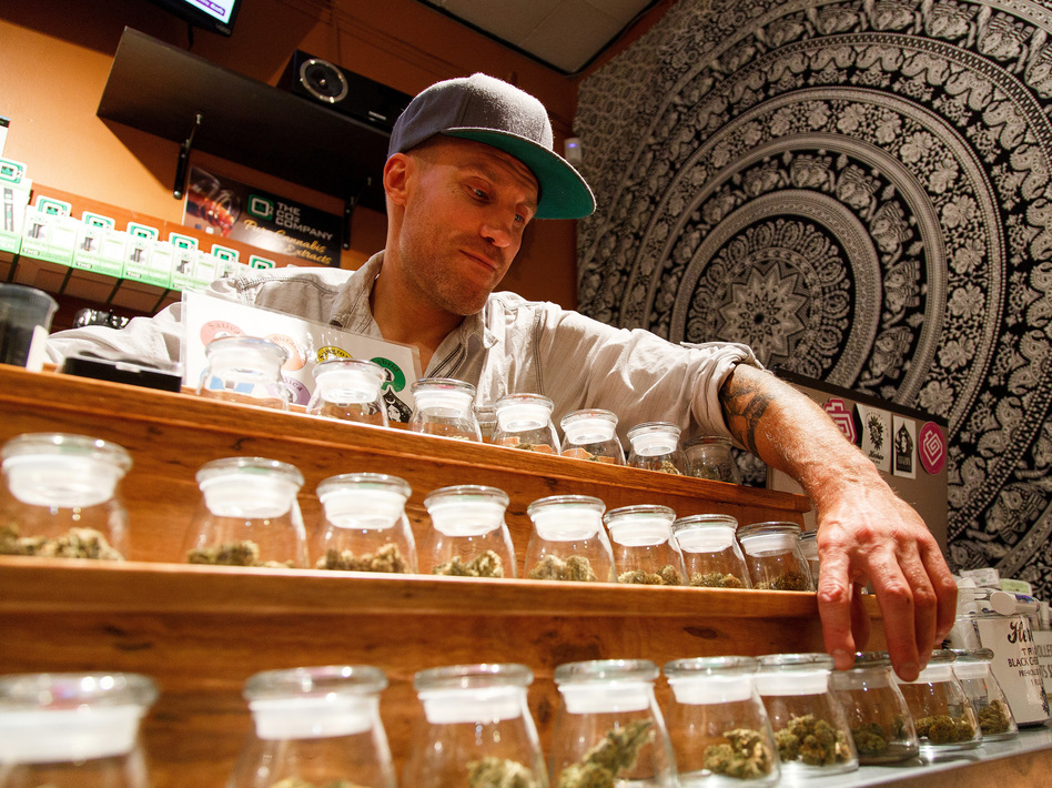 Shane Cavanaugh, owner of Amazon Organics, a pot dispensary in Eugene, Ore., arranges the cannabis display in his store in September 2015. (Ryan Kang/AP)