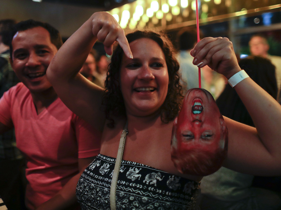 A woman at a bar in Buenos Aires, Argentina, laughs as she holds a mask depicting Donald Trump during an election night party on Nov. 8. (Natacha Pisarenko/AP)