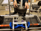 Electrical engineer Doug Lee adds weights to the setup the lab built to test hoverboards.