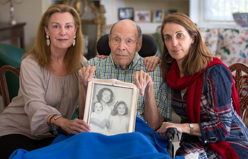Laura Rees (left) and her sister Nancy Fee sit with their father, Joseph Fee, while holding a photo of his late wife, Elizabeth. (Robert Durell for KHN)