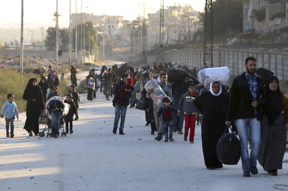 People flee rebel-held eastern neighborhoods of Aleppo into the Sheikh Maqsud area, controlled by Kurdish fighters, in Syria on Sunday. The photo was provided by the Rumaf, a Syrian Kurdish activist group, and authenticated by The Associated Press. (The Rumaf/AP)