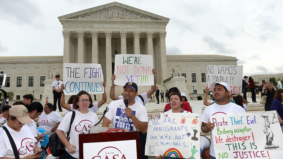 People attend an immigration rally outside the Supreme Court in June.