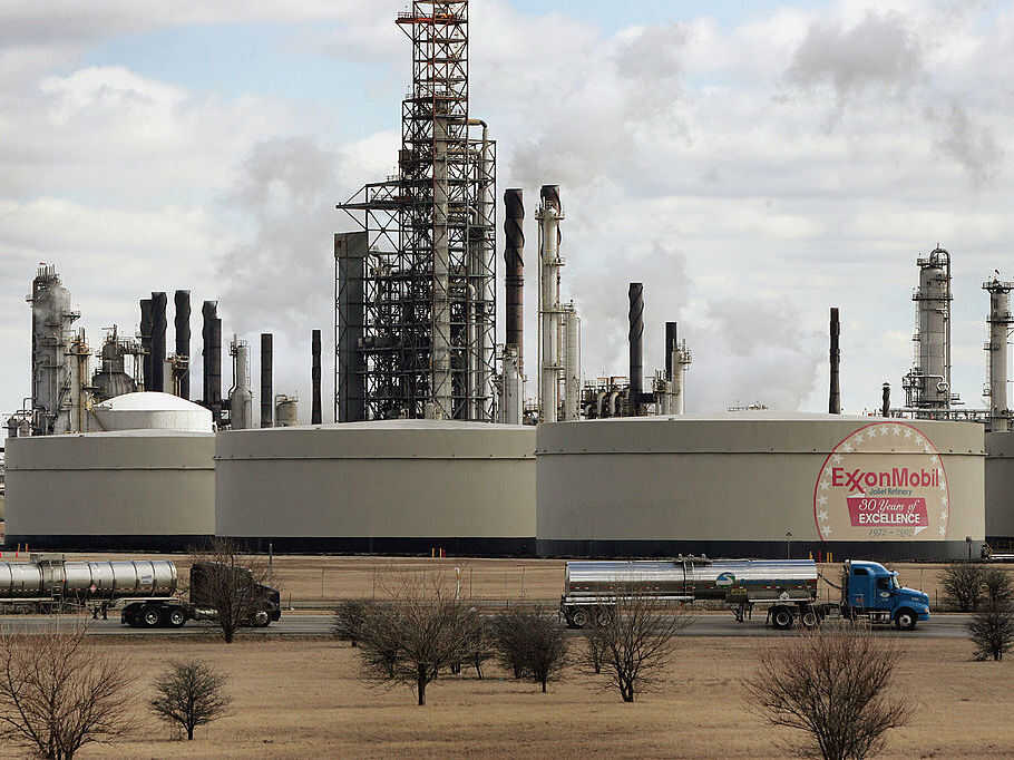 Tanker trucks drive past an ExxonMobil oil refinery on March 8, 2005, in Joliet, Ill.