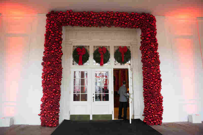 Wreathes and red ornaments adorn this entrance to the White House.