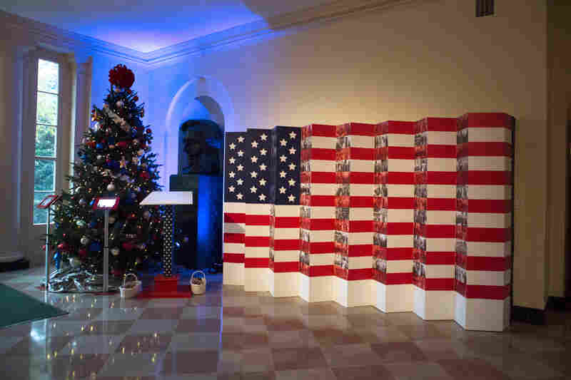 Inspired by the First Lady and Dr. Joe Biden's Joining Forces initiative, a giant flag installation features images of the First Family with military members. It's presented next to the military tree that is adorned with gold stars to honor the fallen and iPads with which guests can send messages to servicemen.