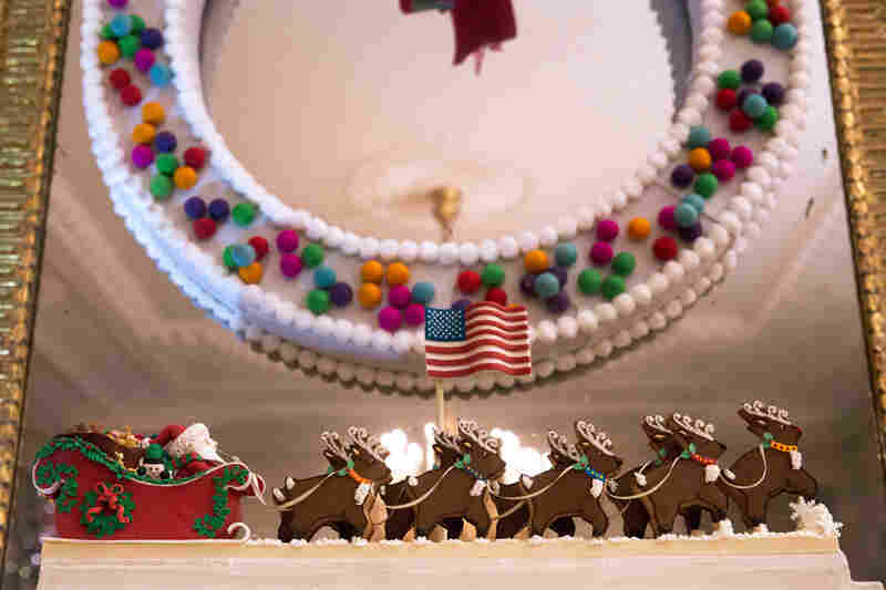 The top of the White House Gingerbread House features Santa in his sleigh with his reindeer leading the way.