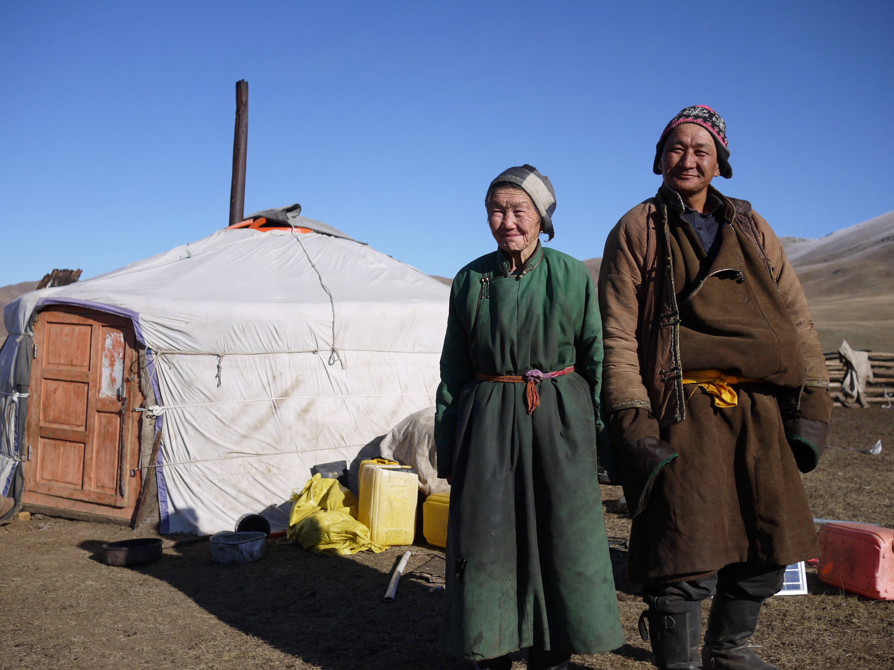 Nomadic herders Lkhagvajav Bish, 90, and her son, Tsahiur Rentsenkhorloo, stand outside their ger in northeastern Mongolia. 'All I can do is watch my grassland disappear,' says Bish. Rob Schmitz/NPR.