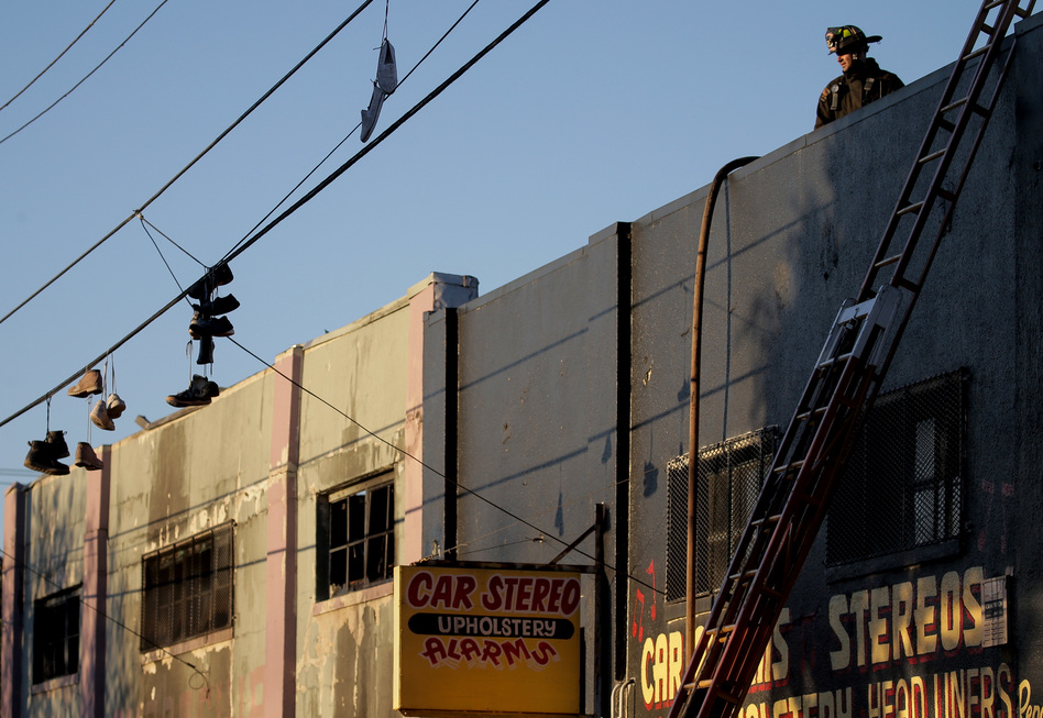 On Saturday, firefighters investigate the scene of the overnight fire at the Ghost Ship warehouse in the Fruitvale neighborhood of Oakland. (Elijah Nouvelage/Getty Images)