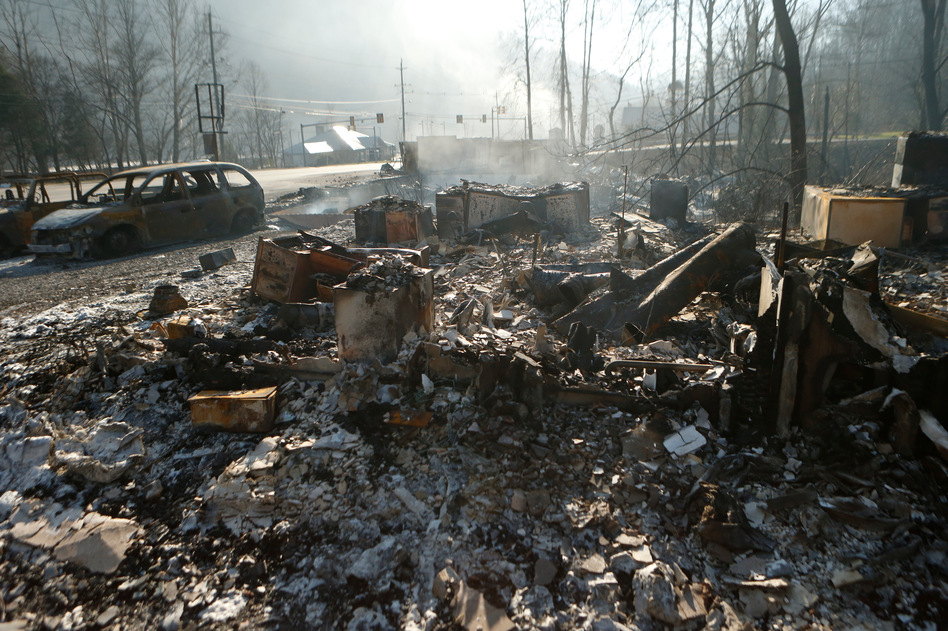 The remains of a business in Gatlinburg, Tenn., smolder on Nov. 29, after a devastating wildfire damaged or destroyed more than 2,000 buildings and killed at least 14 people. (Brian Blanco/Getty Images)