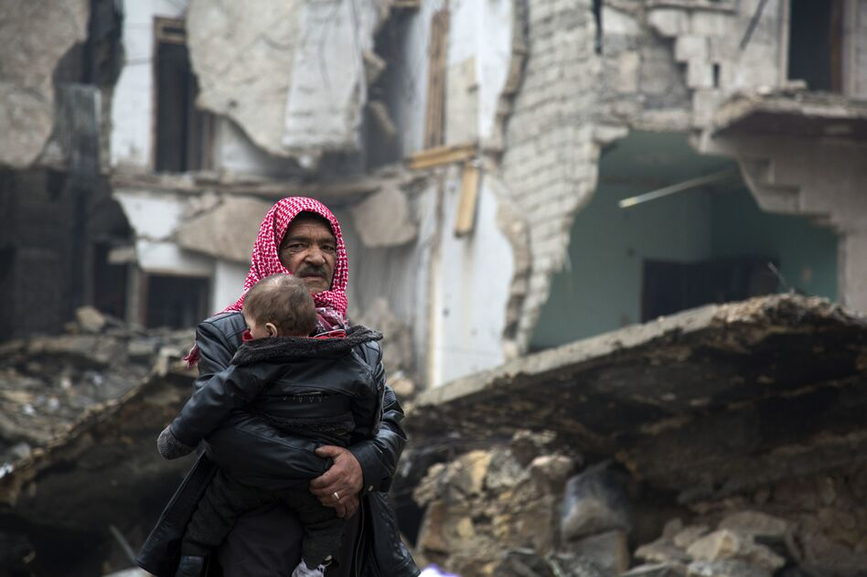 Syrians leave a rebel-held area of Aleppo toward the government-held side on Tuesday, during an operation by Syrian government forces to retake the embattled city. U.N. chief Ban Ki-moon expressed alarm over reports of atrocities against civilians Monday, as the battle for Aleppo entered its final phase. (Karam al-Masri/AFP/Getty Images)