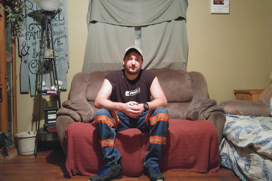 Branham wears reflective mining pants in his home in Elkhorn City, Ky. Branham has advanced stage black lung and was forced to quit mining earlier this year. (Benny Becker/Ohio Valley ReSource)