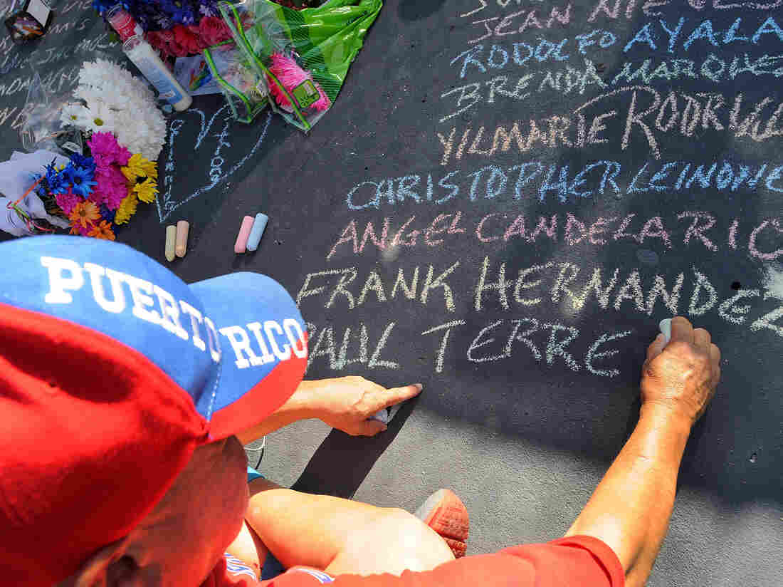 Edwin Rodriguez writes the names of the victims of the Pulse nightclub shooting in front of the club on June 21, 2016 in Orlando, Florida.