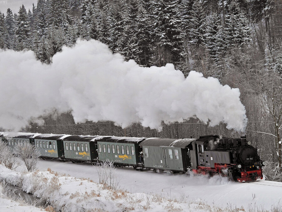 a steam engine makes its way through a snowcovered landscape