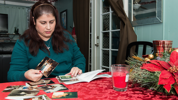 Rosemary Navarro, 40, looks through old childhood photographs at her home in La Habra, Calif. Her mother, Rosa Maria Navarro, passed away in 2009 from Alzheimer