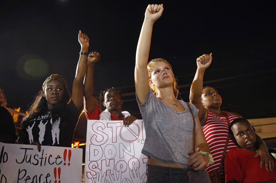 Mourners raise their fists during a night rally in honor of Alton Sterling outside the Triple S Food Mart in Baton Rouge, La., on July 11. Sterling was one of several men killed in police shootings this year. (Gerald Herbert/AP)