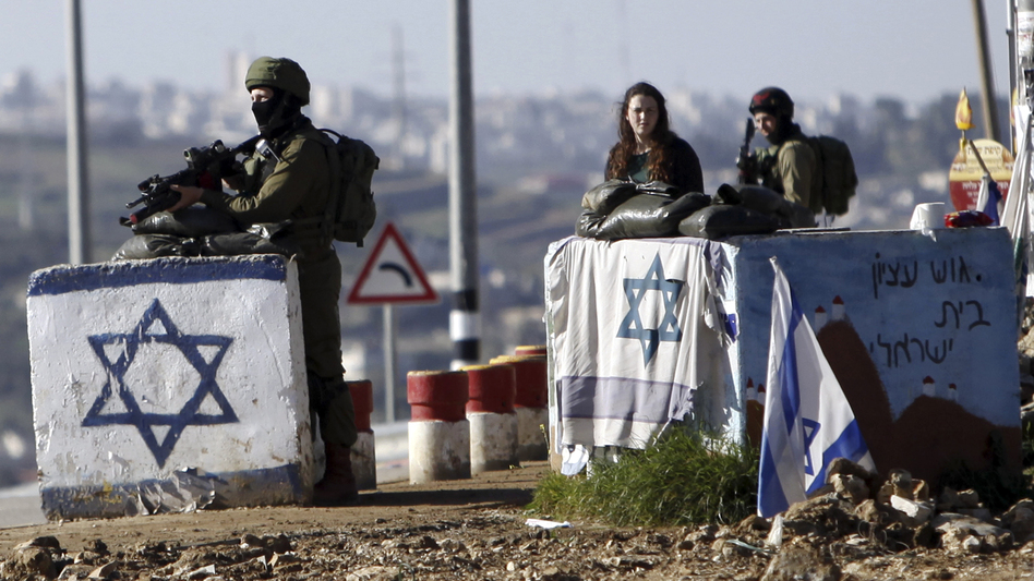 The U.N. Security Council has condemned Israel's construction of settlements, with Ambassador Samantha Power saying the project hurts Israel's security. In this photo from March, soldiers guard the Gush Etzion junction near a cluster of settlements in the West Bank. (Mahmoud Illean/AP)