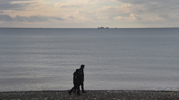 Russian police patrol the shores along the Black Sea at Sochi on Monday, one day after a Russian military plane crashed into the sea. An extensive search effort has revealed no sign of survivors among the 92 on board.