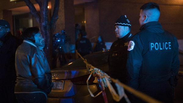 A woman talks with members of the Chicago Police Department at the scene where at least six people were shot on Sunday. Dozens of people were shot over the holiday weekend in Chicago.