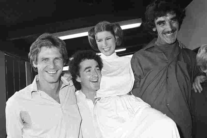 Carrie Fisher (second from right), who played Princess Leia in the movie Star Wars, is pictured with co-stars (left to right) Harrison Ford, who played Han Solo; Anthony Daniels, who played C-3P0; and Peter Mayhew, who played Chewbacca the Wookiee, as they take a break from filming a television special in 1978.