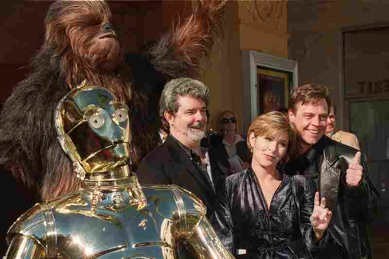 Characters from Star Wars join writer and director George Lucas (center) and actors Carrie Fisher and Mark Hamill at the world premiere of Star Wars Special Edition, in 1997.
