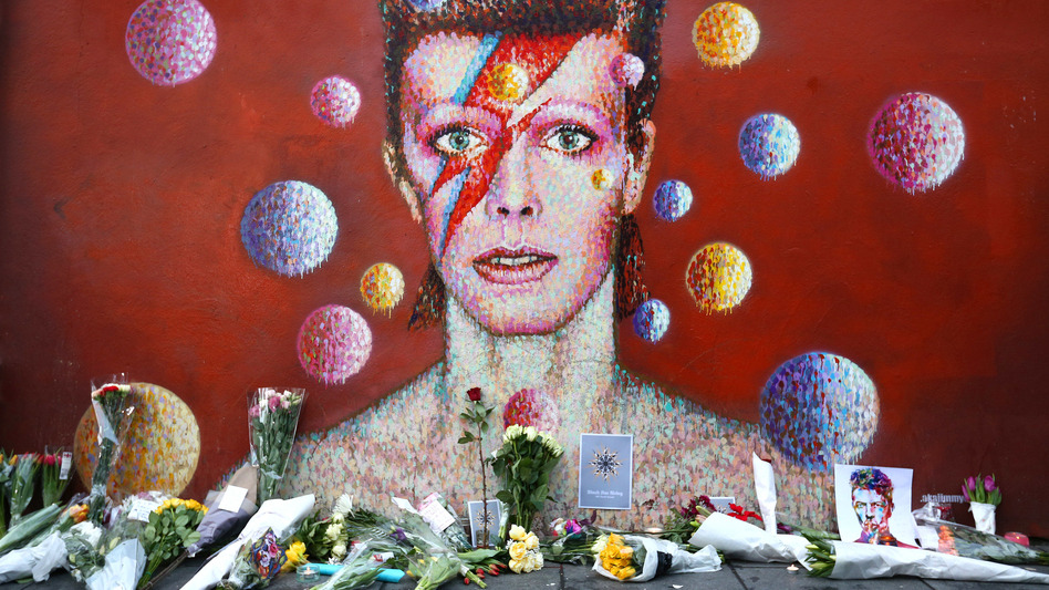 Flowers are laid beneath a mural of David Bowie in London in January. (Getty Images)