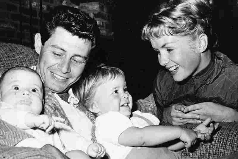 Singer Eddie Fisher and actress Debbie Reynolds cuddle their two children, four-month-old Todd (left) and 19-month-old Carrie, in 1958.