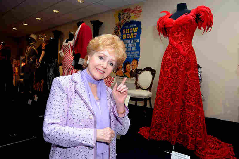 "Debbie Reynolds poses with a costume she wore in the The Unsinkable Molly Brown at The Paley Center For Media's Reception For ""Debbie Reynolds: The Exhibit"" in 2011 in Beverly Hills, Calif."
