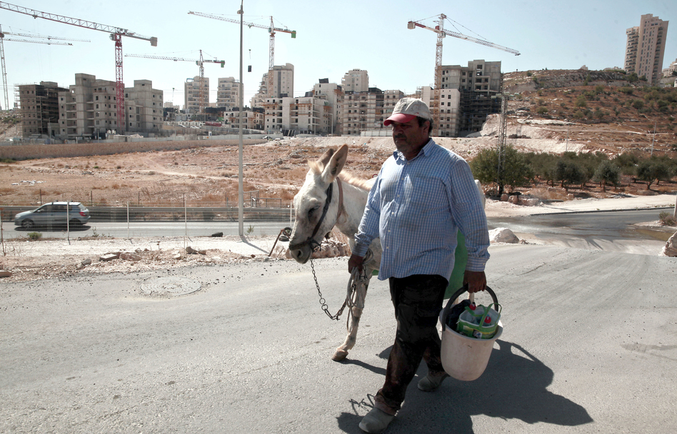A Palestinian man walks near a construction site for new Israeli housing in the East Jerusalem neighborhood of Har Homa in September. The Palestinians claim East Jerusalem as a capital of a future state and object to Israeli building in the eastern part of the city and throughout the West Bank. Israel claims all of Jerusalem as its capital. (Mahmoud Illean/AP)