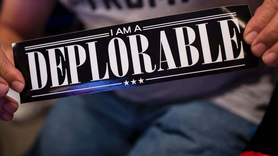 """A supporter of Republican presidential candidate Donald Trump shows a bumper sticker reading """"I am a Deplorable"""" at Mohegan Sun Arena in Wilkes-Barre, Pa., on Oct. 10. The term references comments by Hillary Clinton that suggest some Trump supporters are """"deplorables."""" (Dominick Reuter/AFP/Getty Images)"""
