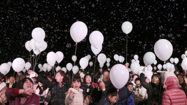 Bubbles float over visitors during a New Year
