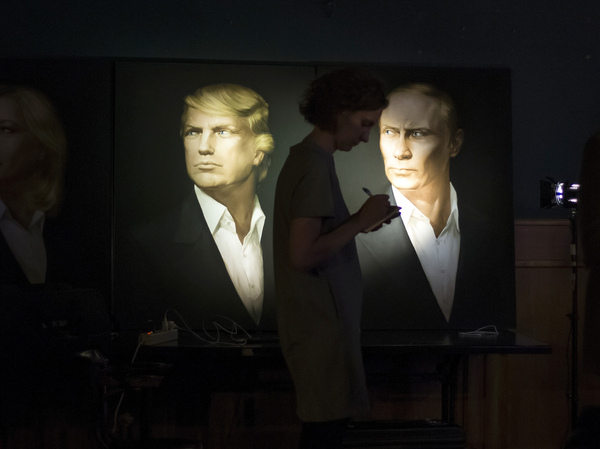 A journalist in Moscow writes notes as she watches a live telecast of the U.S. presidential election standing in front of portraits of Donald Trump and Russian President Vladimir Putin.
