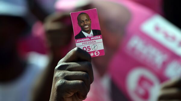 A protester holds a photo of presidential candidate Jovenel Moise near the headquarters of the Provisional Electoral Council in Port-au-Prince last April, as demonstrators demanded that elections be held. Haiti