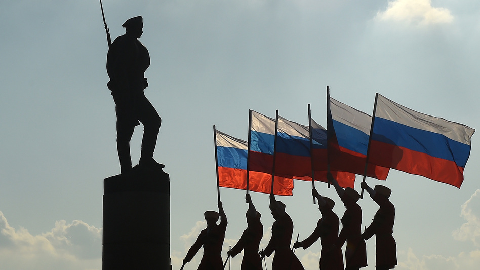 Russians hold their national flag next to a bronze statue of a soldier in Moscow on Aug. 22, 2016, during celebrations of the National Flag Day. U.S. intelligence agencies say Russia is engaged in a widespread disinformation campaign that targets the U.S. and many other countries. (Vasily Maximov/AFP/Getty Images)