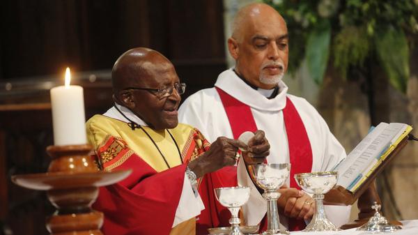 Anglican Archbishop Emeritus Desmond Tutu (left) celebrates mass on his 85th birthday at St. George