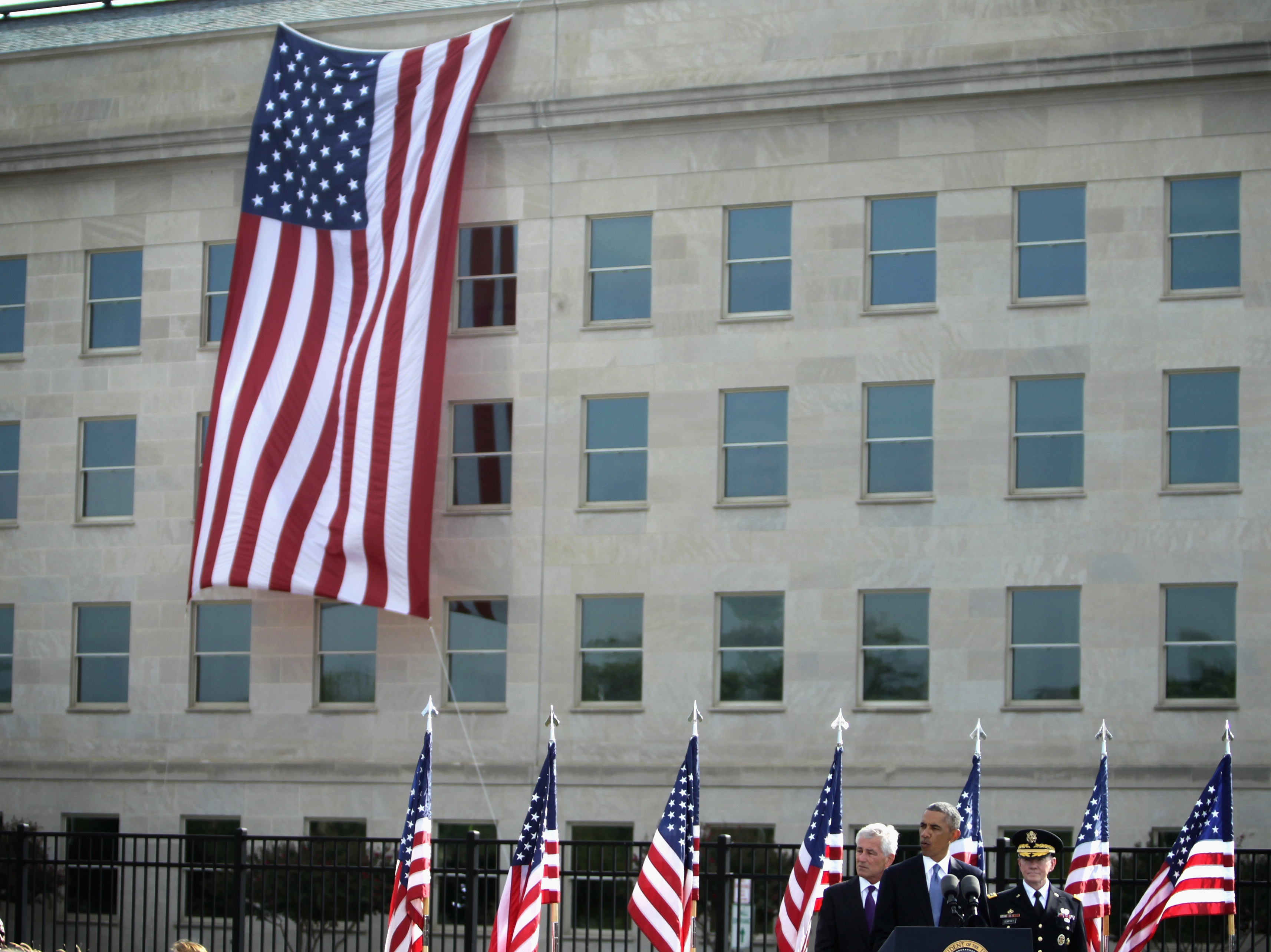 President Barack Obama (2nd L) speaks as Secretary of Defense Chuck Hagel (L) and Chairman of the Joint Chiefs Gen. Martin Dempsey (R) listen during a ceremony to mark the 13th anniversary of the 9/11 terrorists attacks at the Pentagon Memorial September 11, 2014 in front of the Pentagon in Arlington, Virginia. (Alex Wong/Getty Images)