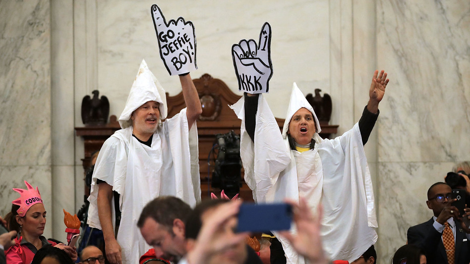 Protesters wearing white sheets shout at Sen. Jeff Sessions as he arrives at the Russell Senate Office Building on Monday for his confirmation hearing. (Getty Images)