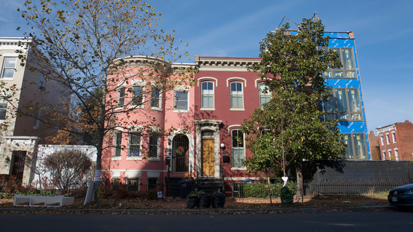 A newer home is undergoing renovations at the end of a block of row houses in the Shaw neighborhood of Washington, D.C. Newcomers began arriving in the neighborhood more than a decade ago.
