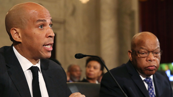 Sen. Cory Booker (left) reads a statement speaking out against Attorney General nominee Jeff Sessions during a Senate Judiciary Committee hearing on Wednesday. Sitting with Booker is Rep. John Lewis.