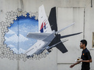 A waiter walks past a mural of Flight MH370 in Shah Alam outside Kuala Lumpur, Malaysia, in February 2016. The flight disappeared nearly three years ago with 239 people on board, and the search for the plane has now been suspended.
