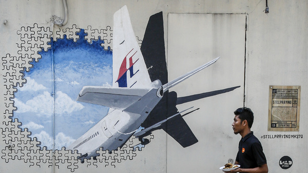 A waiter walks past a mural of flight MH370 in Shah Alam outside Kuala Lumpur, Malaysia, in February 2016. The flight mysteriously disappeared nearly three years ago with 239 people on board, and the search for the plane has now been suspended.
