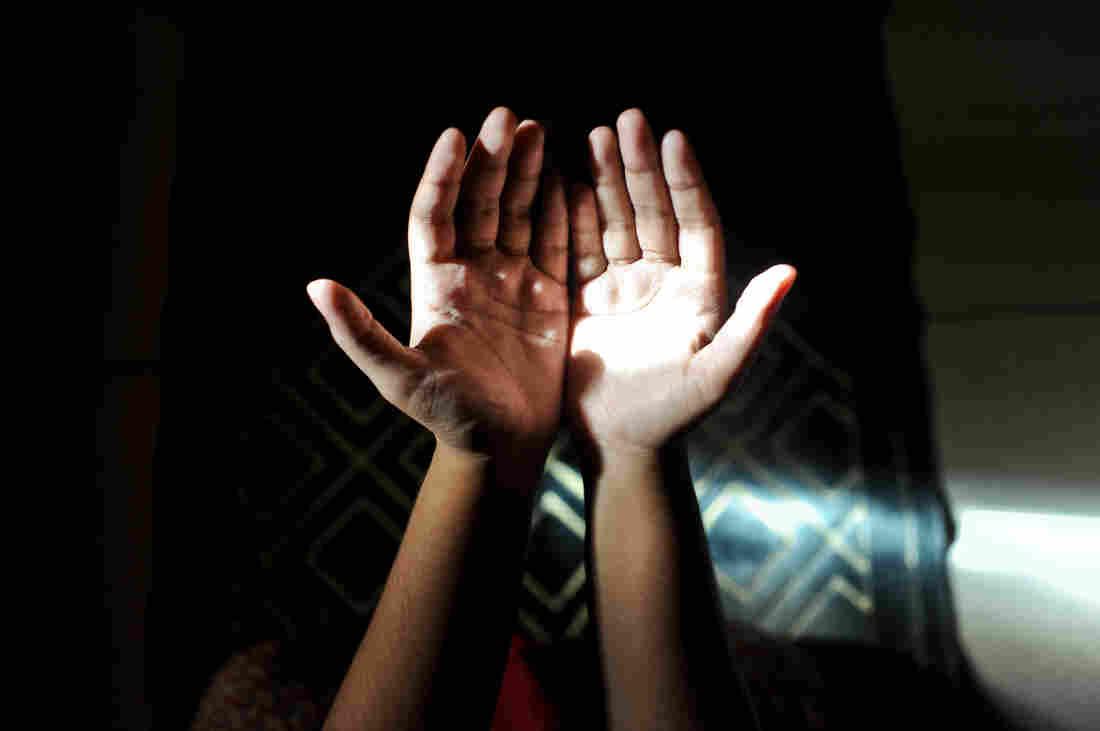 A Muslim woman prays in her home.